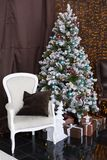 Christmas or New Year room with dressed Christmas tree with blue and brown Christmas balls and candles, decorative gifts wrapped w Royalty Free Stock Photo