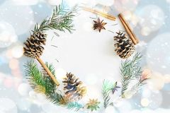 Christmas and New Year round frame composition. Fir branches with cones, star anise, cinnamon on blue background. Christmas round frame composition. Fir branches stock photography