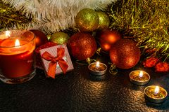 Christmas and new year`s composition of red balls for Christmas trees and Golden tinsel, in the light of candles on a dark backgro royalty free stock image