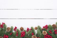 Christmas and New Year`s composition. Top view of spruce branches, pine cones, red berries and bell on white wooden table stock photo