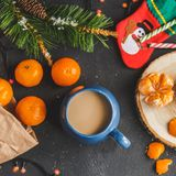 Christmas and New Year`s concept. Mandarins, coffee mug, lollypop, Christmas tree branch. Against a dark background Stock Image