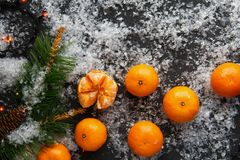 Christmas and New Year`s concept. Mandarins, coffee mug, snow, Christmas tree branch. Against a dark background Royalty Free Stock Photo