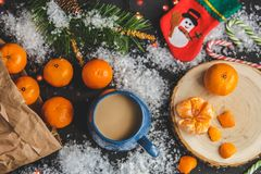 Christmas and New Year`s concept. Mandarins, coffee mug, snow, Christmas tree branch. Against a dark background Stock Image