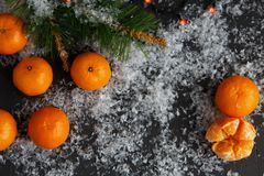 Christmas and New Year`s concept. Mandarins, coffee mug, snow, Christmas tree branch. Against a dark background Royalty Free Stock Photography