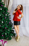 On Christmas and New Year`s Day a woman decorates a Christmas tr Royalty Free Stock Image