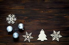 Christmas and New Year`s decor. Decorative wooden snowflakes and silver balls on wooden background, concept of New Year`s holiday. Close-up, copy space royalty free stock image