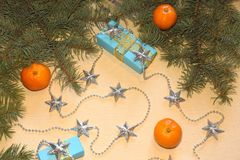 Christmas and New Year`s gifts in blue boxes lie under a Christmas tree next to tangerines and silvery stars. Stock Photography