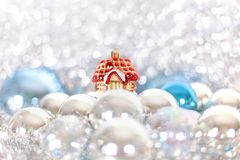 Christmas and New Year`s toy fairy tale red house in snowdrifts and snow of Christmas balls and tinsel in blue and white colors. Holiday decorations, ornaments stock photos