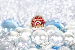 Christmas and New Year`s toy fairy tale red house in snowdrifts and snow of Christmas balls and tinsel in blue and white colors stock images