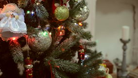 Christmas and New Year's toys on the Christmas tree among the twinkling lights. stock video
