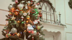 Christmas and New Year's toys on the Christmas tree among the twinkling lights. Beautiful Gift boxes, Christmas, and New Year's toys, balls, snowmen, candles stock video footage