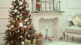 Christmas and New Year's toys on the Christmas tree among the twinkling lights. Beautiful Gift boxes, Christmas, and New Year's toys, balls, snowmen, candles stock footage