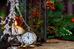 Christmas and New Year s vintage clock showing five to midnight. Festive evening burning candle Stock Photography
