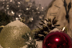 Christmas and New Year`s vintage clock showing five to midnight, toy balls, fir cones Stock Photo