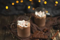 Christmas or New Year's winter hot chocolate with marshmallow in a dark mug, with chocolate, cinnamon and spices with a festive l. Ight garland, selective focus stock image