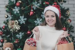 Young caucasian woman wears santacros hat holding shopping bags royalty free stock photography