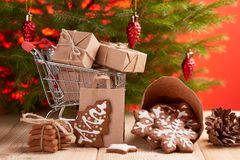 Christmas and New Year shopping. Shopping trolley with gift boxes and gingerbread cookies standing on a wooden table on a red background with Christmas fir tree Stock Photography