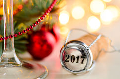 Christmas or new year sparkling wine cork. Sparkling wine or champagne cork on table with christmas or new year blurred background and decorated fir-tree Royalty Free Stock Photography