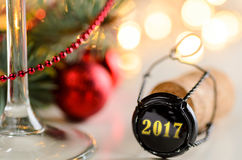 Christmas or new year sparkling wine cork. Sparkling wine or champagne cork on table with christmas or new year blurred background and decorated fir-tree Royalty Free Stock Image