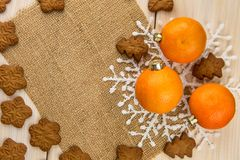 Christmas or New Year tangerines and gingerbread cookies with snowflakes framed on brown sack background texture. Christmas or New Year tangerines and royalty free stock photo
