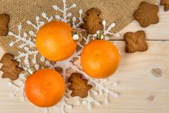 Christmas or New Year tangerines and gingerbread cookies with snowflakes framed on brown sack background texture. Christmas or New Year tangerines and stock photography