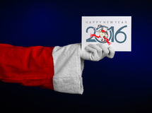 Christmas and New Year 2016 theme: Santa Claus hand holding a white gift card on a dark blue background in studio isolated Stock Images