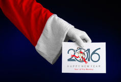 Christmas and New Year 2016 theme: Santa Claus hand holding a white gift card on a dark blue background in studio isolated Stock Photos