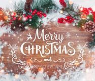 Christmas and New Year typographical on holiday background with Xmas decoration, branch of fir tree and snow. Stock Photo