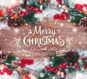 Christmas and New Year typographical on holiday background with Xmas decoration, branch of fir tree and snow. Stock Image