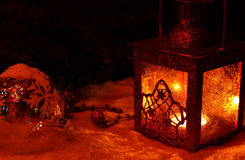 Christmas and New Year wallpapers for desktop. Antique street candle red lamp in winters night on snow and glass Christmas ball Royalty Free Stock Photo