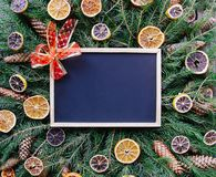 Christmas, New Year winter holiday composition. Empty framed board on green fir-tree branches decorated with dried orange slices a. Empty framed board on green royalty free stock photos