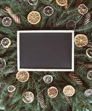 Christmas, New Year winter holiday composition. Empty framed board on green fir-tree branches decorated with dried orange slices a. Empty framed board on green stock image
