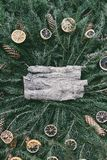 Christmas, New Year winter holiday vintage style composition. Tree bark piece on green fir-tree branches decorated with dried oran. Tree bark piece on green fir stock image