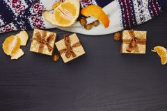 Christmas, New Year or winter holidays composition. Craft gift boxes with ribbon, tangerines, hazelnuts and warm knitted sweater stock images