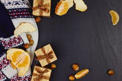 Christmas, New Year or winter holidays composition. Craft gift boxes with ribbon, tangerines, hazelnuts and warm knitted sweater stock image
