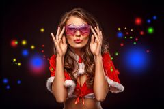 Christmas and New Year. Woman in santa costume and fancy glasses standing on brown pouting lips close-up. Young woman wearing santa costume and fancy eyeglasses stock images