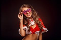 Christmas and New Year. Woman in santa costume and fancy glasses standing isolated on brown smiling cheerful close-up. Young woman wearing santa costume and royalty free stock photos