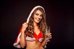 Christmas and New Year. Woman in santa costume with hood standing on black with glass of champagne smiling. Young woman wearing santa costume with hood standing stock photography