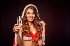 Christmas and New Year. Woman in santa costume with hood standing isolated on black with glass of champagne close-up. Young woman wearing santa costume with hood stock image