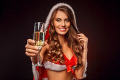 Christmas and New Year. Woman in santa costume with hood standing isolated on black with glass of champagne close-up. Young woman wearing santa costume with hood royalty free stock photography