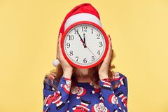Christmas New Year. Woman in Santa hat with Clock. Christmas New Year. Young Woman in Santa Claus hat with Red Clock. Happy Smiling Redhead Girl in Stylish Stock Photography