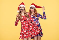Christmas New Year. Woman in Santa hat with Props. Christmas New Year. Young Woman in Santa Claus hat Having Fun Happy with Holiday Props. Fashion. Pretty Stock Image