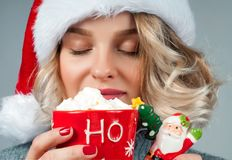 Christmas and New Year.  Woman in santa`s hat is holding a cup of coffee. Stock Image
