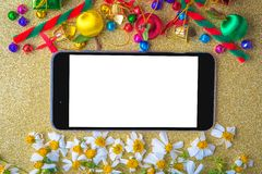 Christmas and new year wooden background banner with blank smart phone , gift box, daisy flower, candy ball and decoration on gold Stock Photo