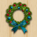 Christmas and New Year wreath. Green branch of fir with red, blue balls and blue bow on wood background. Christmas cards Royalty Free Stock Image