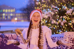 Christmas. New Year. Young cheerful girl in a red cap at the par Royalty Free Stock Photos