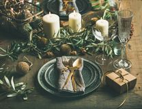 Christmas or New Years eve celebration party table setting. Plates, golden cutlery, festive branch decoration, candles and gliterring toys over wooden table Royalty Free Stock Photos