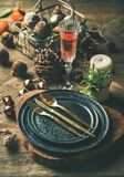 Christmas or New Years eve holiday table setting. Plates, silverware, champaigne in glass, candle and toy festive decorations over vintahge table background Royalty Free Stock Photos