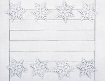 Christmas or New Years Snowflake Borders on White Wood Boards Background with copy space in the middle.  It`s horizontal but will