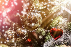 Christmas and newyear festive concept. Closeup of Christmas-tree with decorations items in light and bokeh background with light flare effect christmas and Stock Images